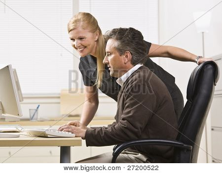 Attractive male and female working on computer. Female standing over male sitting at desk. Looking at computer. Horizontal