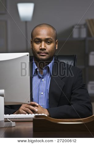 A young businessman is working on his computer at the office.  He is looking at the camera.  Vertically framed shot.