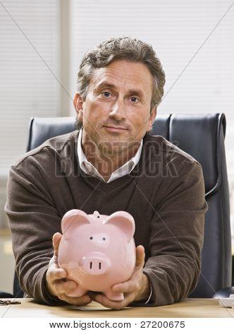 Um empresário está sentado em uma mesa em um escritório e está segurando um cofrinho.  Ele está olhando para o ca