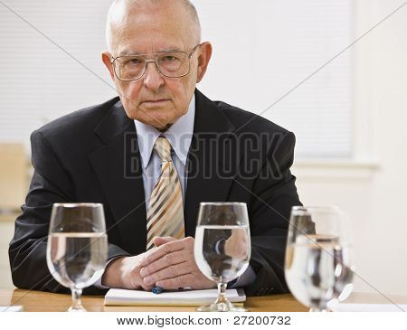 An elderly businessman is seated at a desk in an office and is looking at the camera.  Horizontally framed shot.