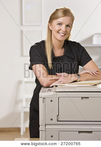 A businesswoman is standing in an office near the copy machine.  She is smiling at the camera.  Vertically framed shot.
