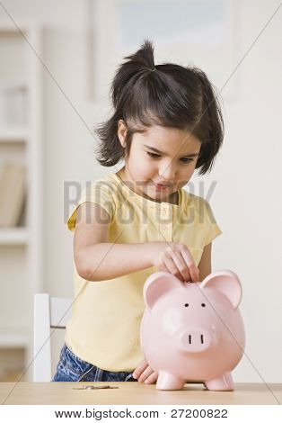 A young girl is playing with a piggy bank.  She is looking away from the camera.  Vertically framed shot.