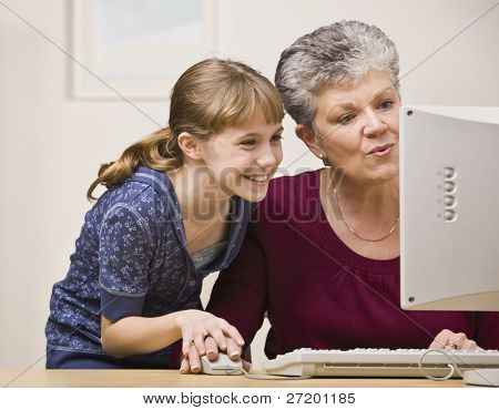 A senior woman and a young girl share a mouse as they use a computer together.