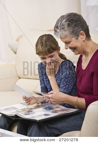 A grandmother looking through a photo album with her granddaughter.  They are both smiling.  Vertically framed shot.