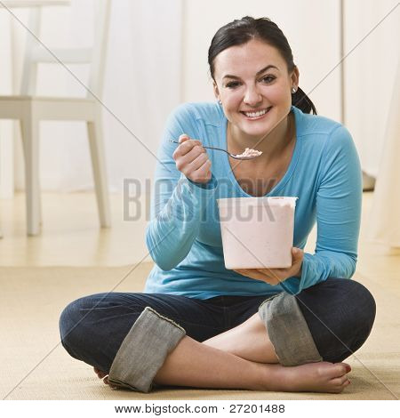 Attractive woman sitting on floor with crossed legs and eating ice cream. Square