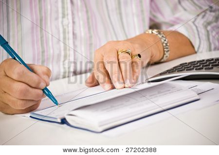 Senior Woman writing Kontrollen