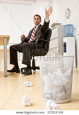 Businessman throwing paper in trash basket