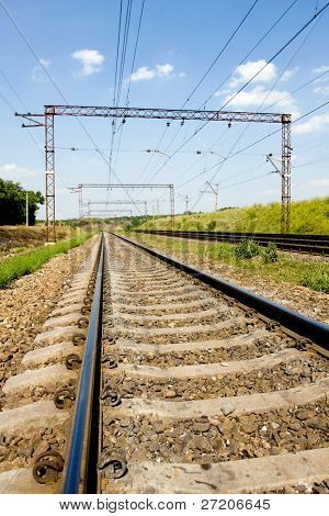 Railway details - rails, sleeper and electric wiring on columns. Shoot in Ukraine
