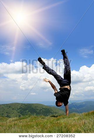 Happy man in mountains stay head over heels on hand