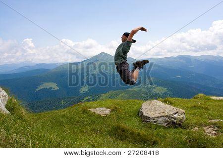 Homem pulando nas montanhas