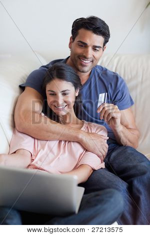 Portrait of a couple booking their holidays online in their living room