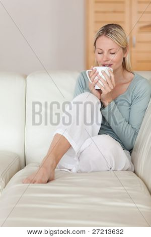 Young woman on the sofa taking a sip of coffee