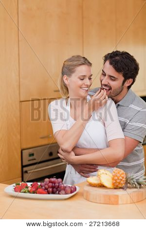 Portrait of a young couple eating fruits in their kitchen
