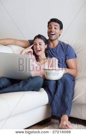 Portrait of a laughing couple watching a movie while eating popcorn with a laptop