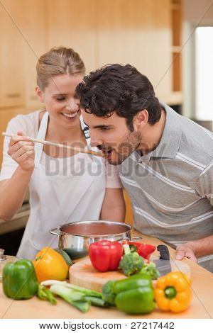 Portrait of a young couple preparing a sauce in their kitchen