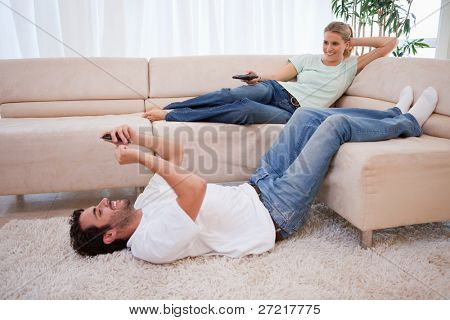 Woman watching television while her husband is using his cellphone in their living room