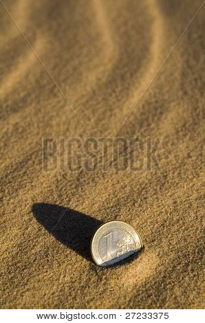 Euro coin in the sand