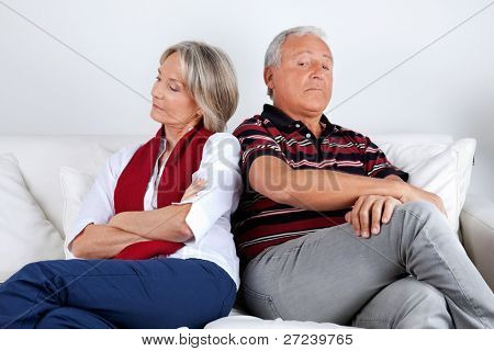 Senior couple sitting on sofa after argument