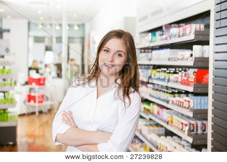 Portrait of female pharmacist standing with arms crossed at pharmacy store