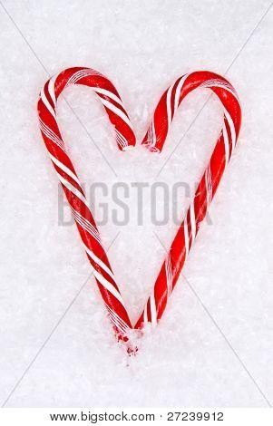 Candy cane coração situa-se na neve que simbolizam o amor