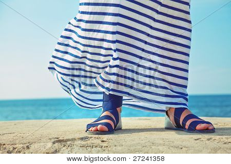 female feet in billowing dress against the background of the ocean