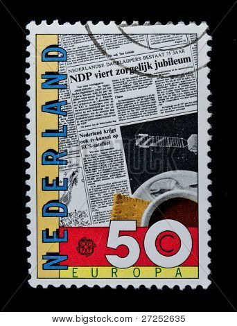 NETHERLANDS - CIRCA 1990s: A stamp printed in the Netherlands shows daily newspaper and morning cup of coffee, circa 1990s