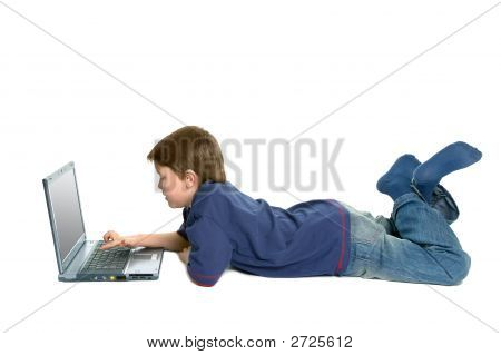 Boy Laying Down Using A Laptop