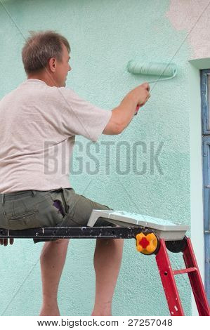 man paints wall with a roll in green outdoor