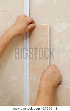 tiling - man installs ceramic tile