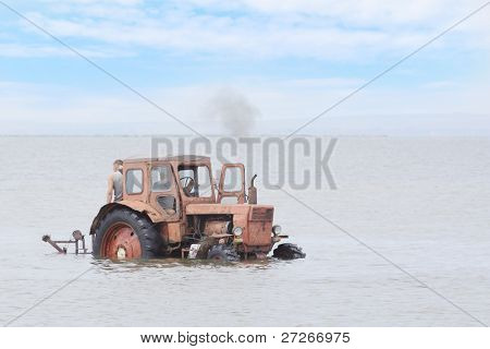 The image of tractor drives under the water