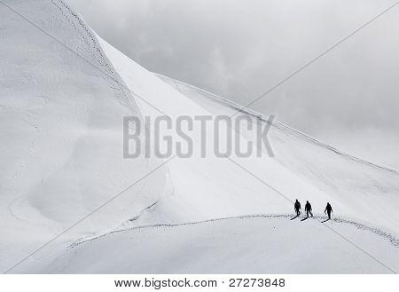 Team of three alpinists climbing a mountain