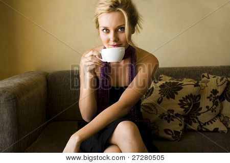 young girl at a cafe drinking coffee