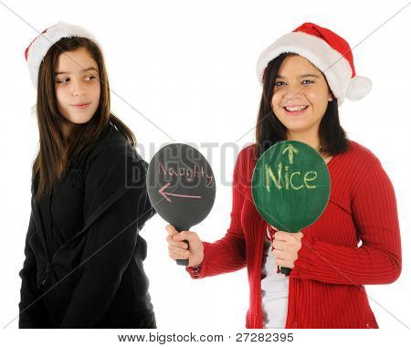 A young teen holding signs that indicate she's nice while her tween sister is naughty.  Both wear Santa hats.  On a white background.