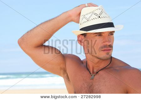 Muscular man posing on the beach in a panama hat