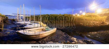 verwerfen Sie Boote auf Schlamm des Flusses mit Stadt Licht Flare in Nacht.