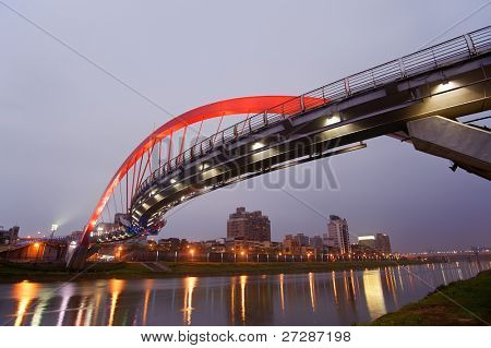 Beautiful bridge in red color over river in evening, city night scene in Taipei, Asia.