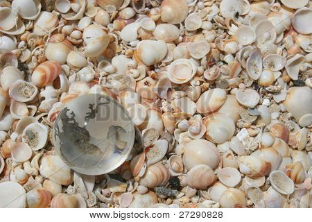 Glass Globe on the background of sea sand