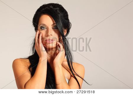 brunette smart woman looks inscrutable and touching her face