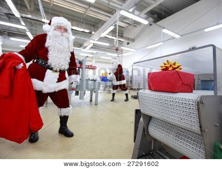 InChristmas gifts - factory. One  santa claus with big sack is waiting for present, the other one is working at production line.