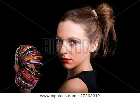 Gorgeous young woman wearing bracelets on black background