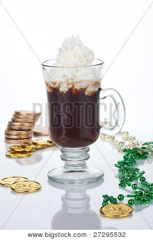 Mug of Irish Coffee with green sprinkles and clover leaf surrounded with gold coins and shamrock ornament for St Patrick's Day