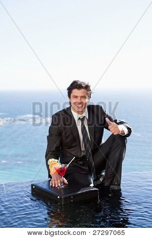 Portrait of a businessman posing with a cocktail on a briefcase with the thumb up
