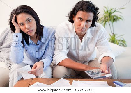 Young couple calculating their costs
