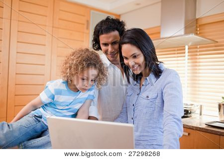 Happy young family surfing the internet in the kitchen together