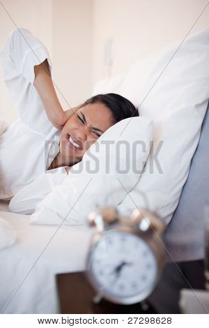 Side view of young woman getting ungently woken by alarm clock