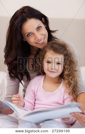 Smiling young mother reading a bedtime story with her little daughter