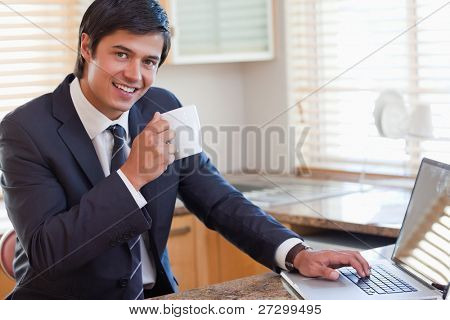 Man working with a notebook while drinking coffee in his kitchen