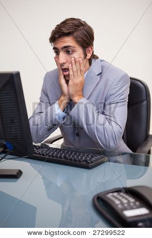 Young businessman getting negative surprised by his computer