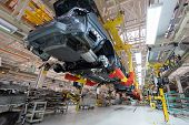Transfer Of Car Body Bottom View. Robotic Equipment Makes The Assembly Of Car. Modern Car Assembly A poster