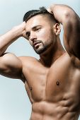Strong Athletic Man Showing Muscular Body And Sixpack Abs Over White Background. Sexy Naked Torso. P poster